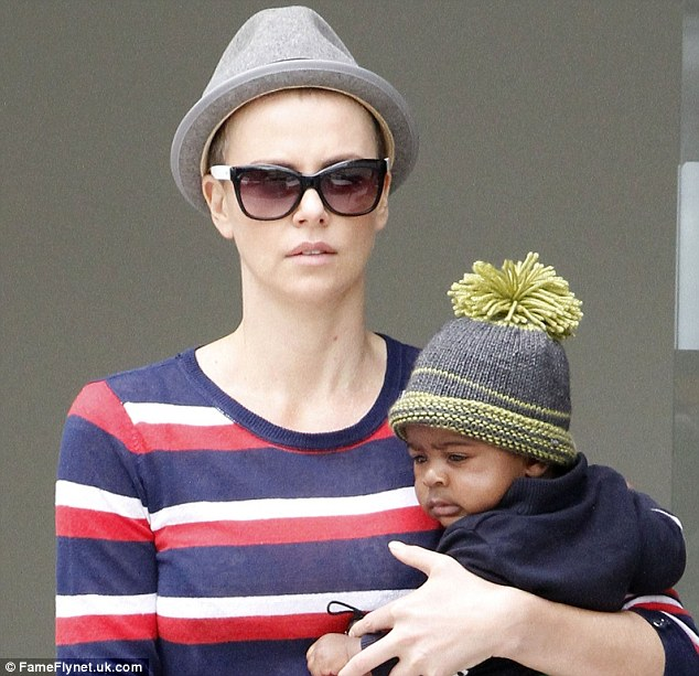 The bald truth: Charlize first stepped out with shaven locks under a pork pie hat in Beverly Hills on Monday with son Jackson