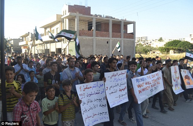 Demanding change: Demonstrators in Kafranbel, near Idlib hold a placard (left) that reads: 'Are you dumb? Is there any sane person who really believes there could be a peaceful solution?'