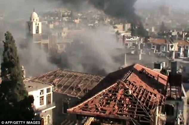 Conflict continues: An image grab taken from a video uploaded on YouTube on Monday shows smoke billowing from the flashpoint Syrian city of Homs which activists said was being attacked by regime forces