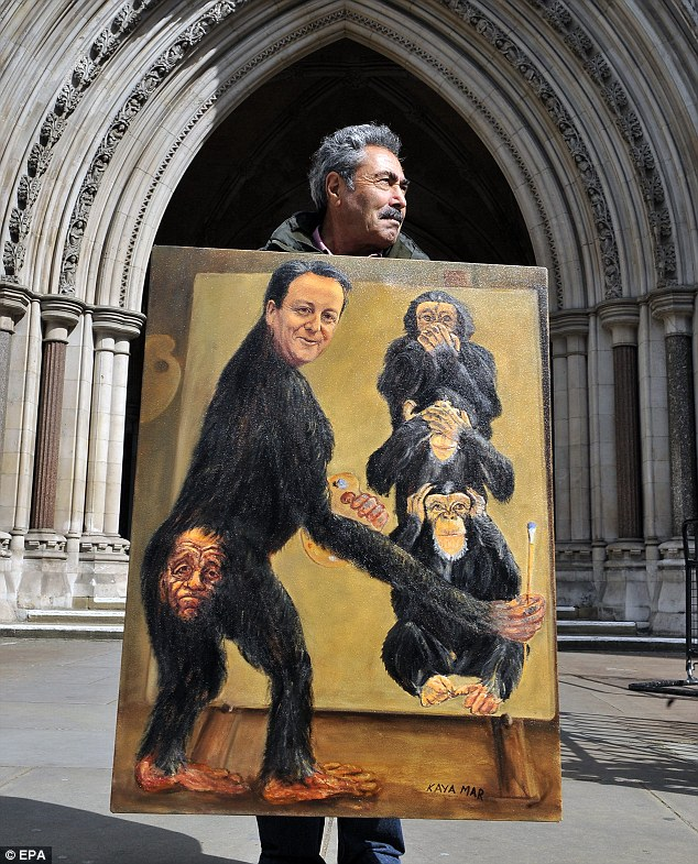 Satirical artist Kaya Mar protests in front of the High Court with his painting of David Cameron as a monkey