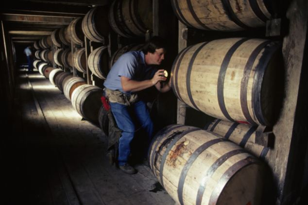 A worker at the Jack Daniels distillery in Lynchburg, Tennessee, checks some of the whiskey aging barrels