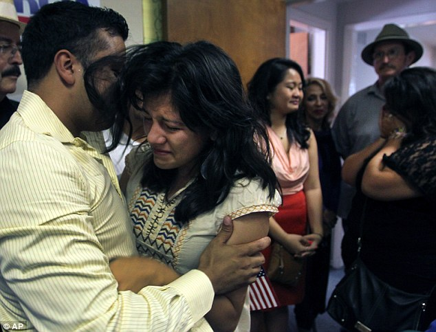 Life changing: Immigrants celebrate Obama's policy, which allows them to stay in the country if they meet certain requirements. Here, Lorena Tule-Romain, right, embraces Ramiro Luna in Oak Cliff, Texas