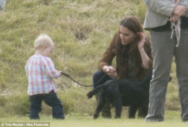 A patient Kate shows 18-month-old Savannah Phillips how to hold Lupo's leashSavannah