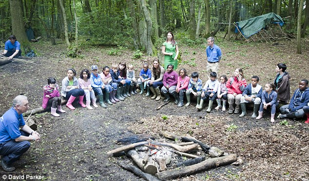 Outdoor type: Kate sits around the campfire with the group of schoolchildren