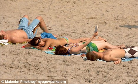 Row: Topless beachgoers sunbathe on a Rockaway beach much to the frustration of local families