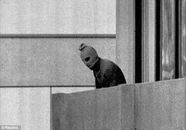 Chilling: One of the terrorists wearing a ski mask on the balcony outside the Israeli contingent's apartment
