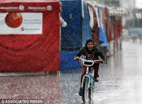 Event: Sumaya Gabbar, 11, pictured, rode her bike through rain at the event where protestors rallied