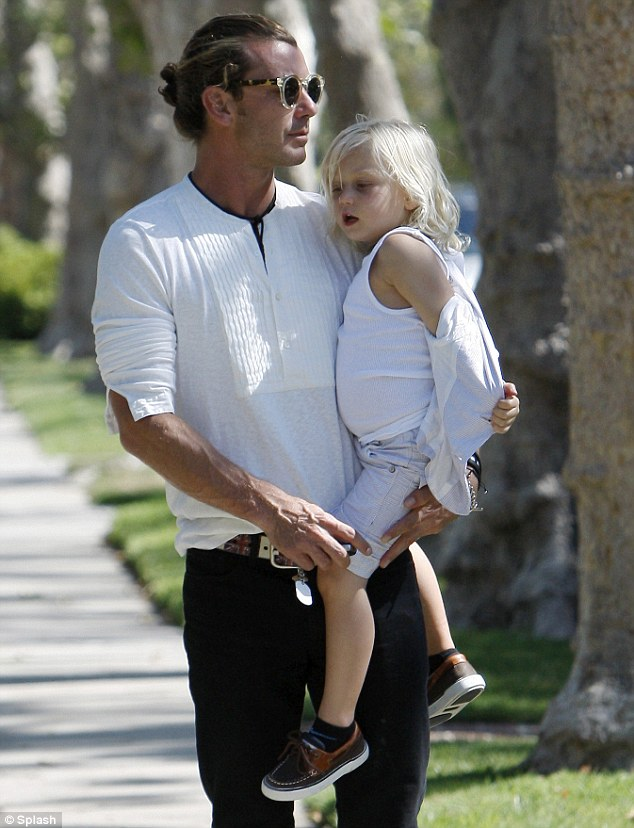 Daddy's boy: The blonde child seemed tired and let his father carry him as he removed his jacket