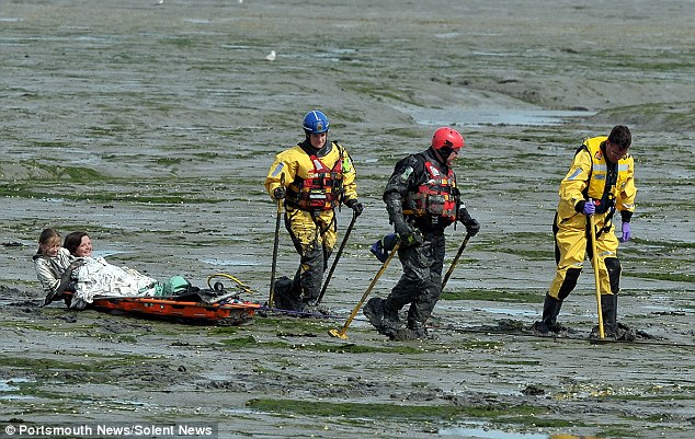 Sliding to safety: The girls are dragged back into the harbour by the coastguard workers where they were put in an ambulance
