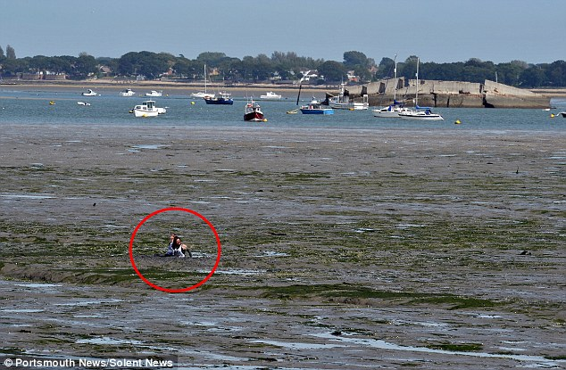 Stranded: The two girls can just about be seen stuck in thick mud in the harbour in Portsmouth, Hampshire, 300ft out