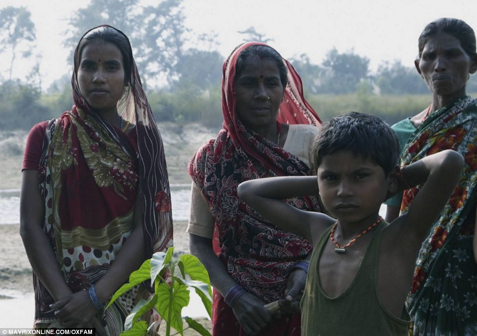 Flooding: Three women and boy stand in front of drenched fields in Nepal