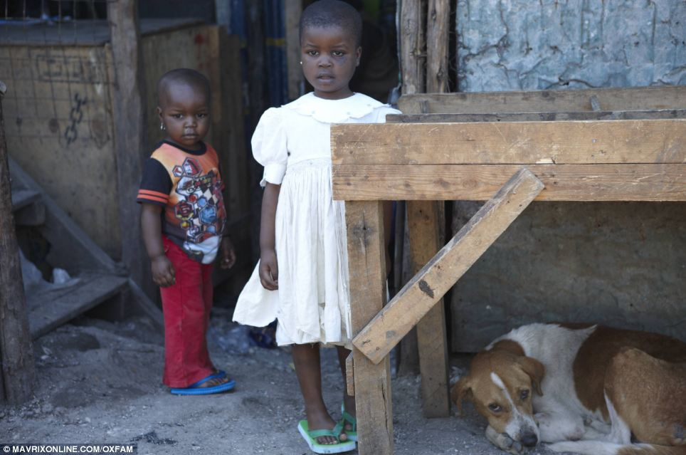 Dusty: Brother and sister seem distracted as they stand on the dusty soil outside their home with a sleepy looking dog