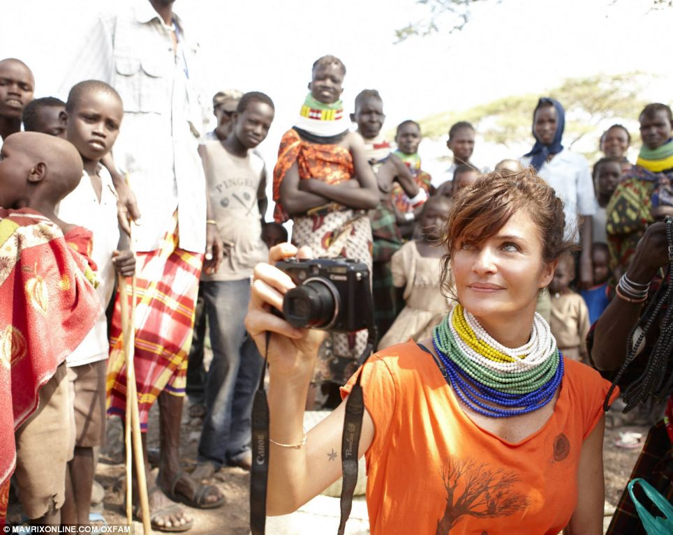 Colourful: Helena Christensen dons a traditional beaded necklace as she photographs a village affected by drought in Kenya