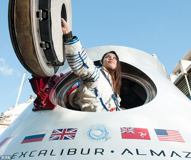Ready for the moon: Jenn Sander, wearing a spacesuit once worn by US Astronaut Peggy Whitson, sits inside a re-entry capsule owned by Excalibur Almaz