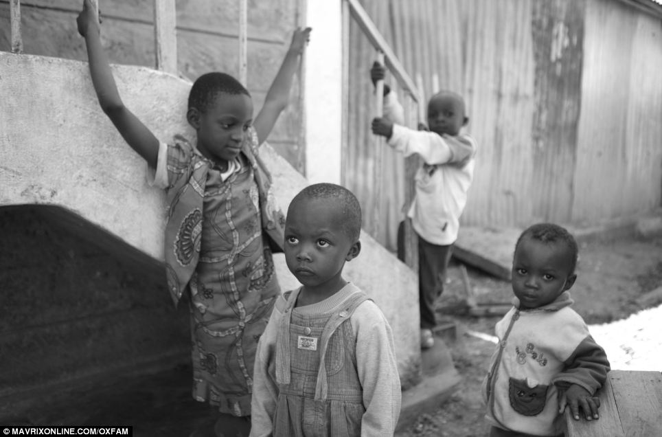 Innocent: Young boys play together in Kenya. One looks at an unseen adult with wide-eyes while another directs his gaze towards the camera
