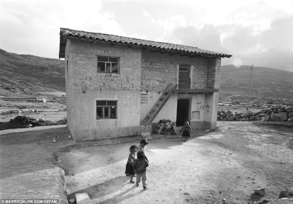 Home: Three girls play together next to a building in Peru. One of their party makes her way into the two story house wearing a thick hooded jacket