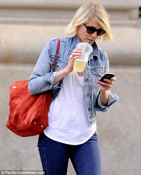 Multitasking: Cameron was seen enjoying the sunshine in the city, checking her phone and drinking a cool iced beverage