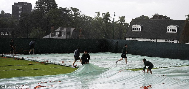 Water nightmare: A shower forced the ball boys and girls to run for the covers
