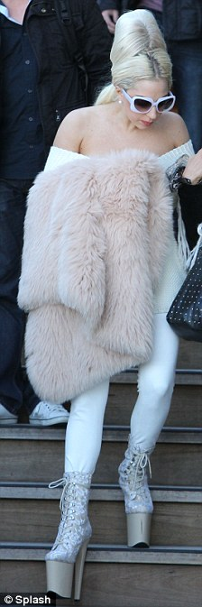 Easy does it! The blonde singer wore towering platform boots, an off the shoulder jumper and carried a fur garment as she left her hotel