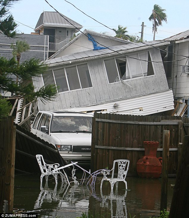 Ravaged: Tropical Storm Debby lifted this Florida home from its foundation next to a flooded yard as the strong winds and driving rain