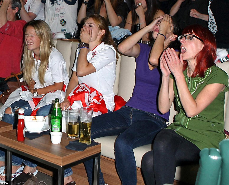 Disaster: England are out after being beaten 4-2 on penalties. Here four fans watch the match in a bar in Leicester Square, London