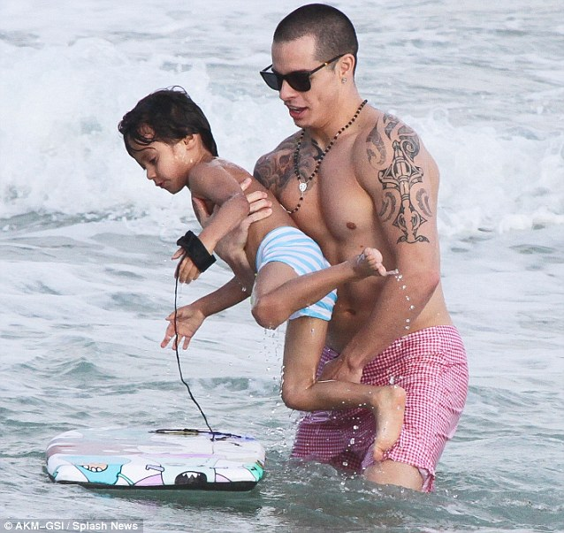Hands on stepfather: The heavily tattooed Casper looked like a natural as he helped Max enjoy his mini bodyboard