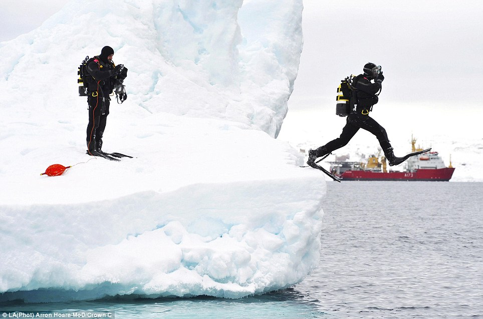 Taking the plunge: A navy diver leaps from an iceberg near the Antarctic Peninsula, while a colleague looks on