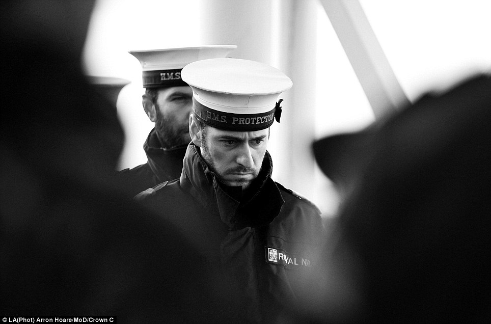 Sombre: Crewmembers have a moment of quiet reflection for fallen colleagues from the Falklands in this thought-provoking image
