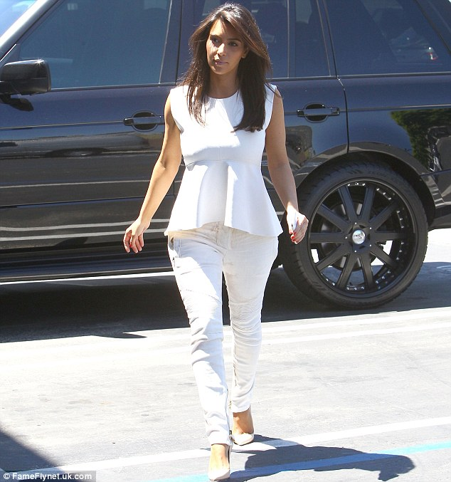 The woman in white: Kim cut a striking figure in her all-white ensemble as she stepped out today