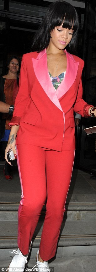 Red hot: Rihanna smartens up her look by stepping out in red suit trousers and a matching scarlet tuxedo