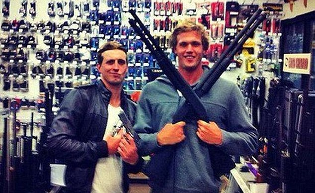 Rebuked: Australian male swimmers Nick D'Arcy and Kenrick Monk pose with guns in a controversial picture that appeared on Facebook