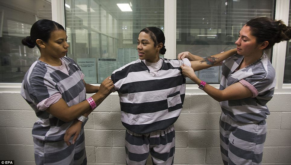Inmates Alma Madrigal (L) and Jennifer Thomas (R) help Lisa McCorvey (C) roll up her sleeves before a day's work