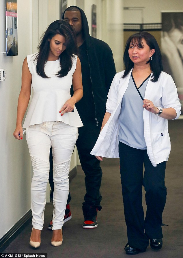 Happy: Kim was jovial as she attended her monthly visit, smiling and chatting to her technician, while Kanye didn't appear too impressed