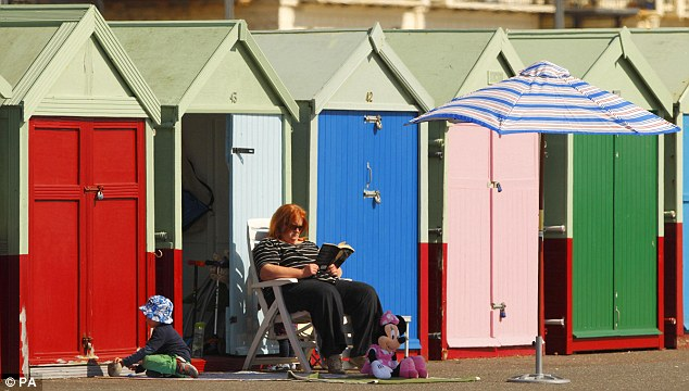 A woman reads a book outside a beach hut in Hove, East Sussex