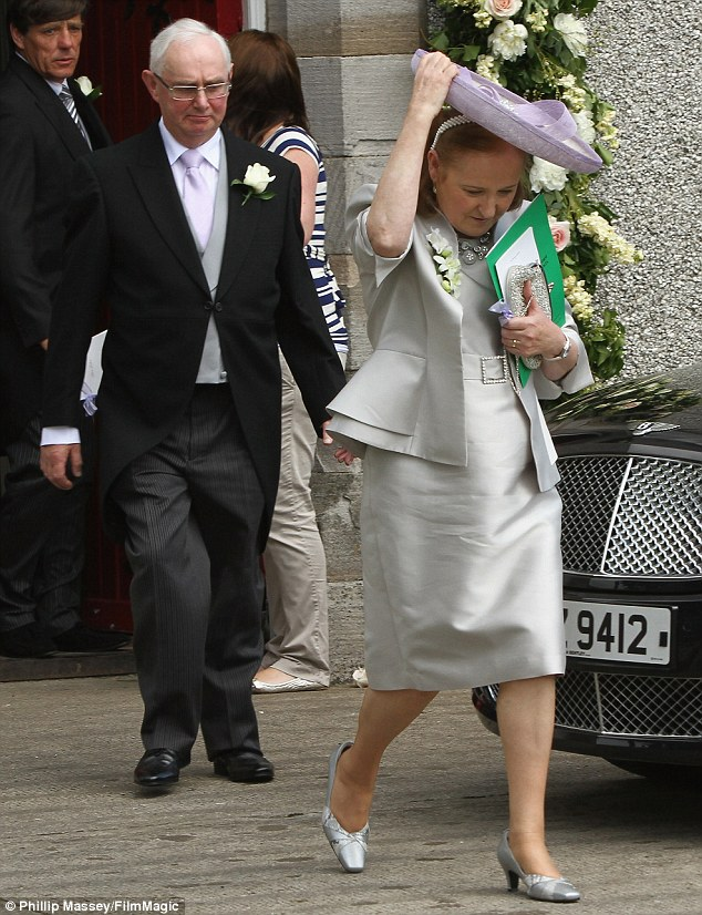 Proud parents: Una's father John looked dapper in his suit while her mother Ann was glamorous in a silver dress and matching jacket at the wedding in Ireland