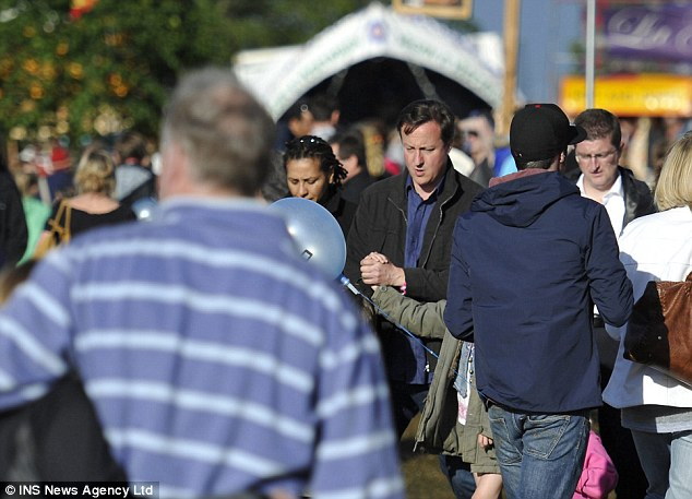 Day out: Mr Cameron can be seen walking through the crowd at the music festival. Among those headlining are Jools Holland,  Elvis Costello, Marc Almond and Alison Moyet