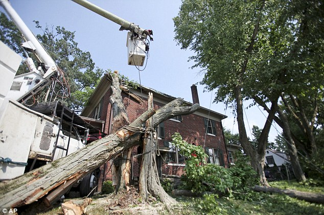 John Sullivan, above, and his father Tony Sullivan, below, of JL Tree Service, work to remove a tree felled by the storm that damaged a house at the corner of Milton and Montrose in Columbus, Ohio on Saturday