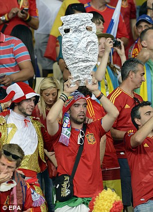 Taking home the trophy: Spanish fans hold a mock version of the European Cup aloft as they soar to victory