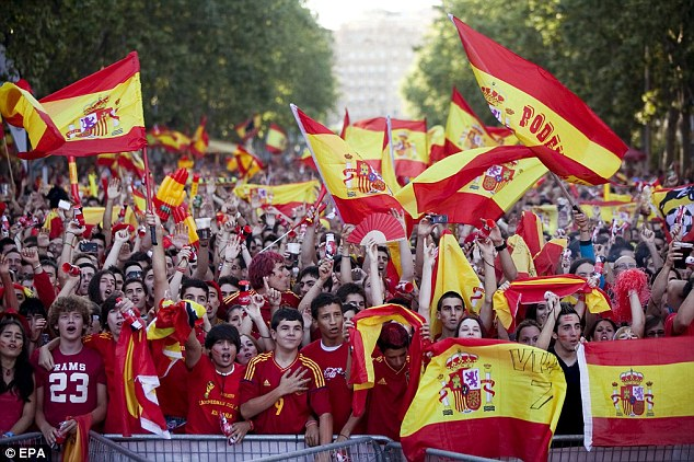 Back home: Spanish fans celebrate victory at a public viewing in Valladolid