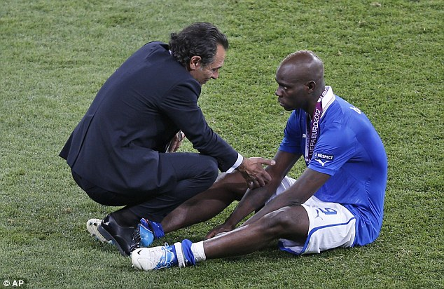 Comforting: Italy coach Cesare Prandelli, left, comforts Manchester City star Mario Balotelli after Italy lose