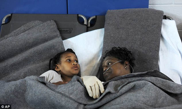 Gimme shelter: Marcia McCloud, right, and her great-granddaughter Makayla Milton, find some comfort at the Red Cross cooling shelter at Sandusky Middle School in Lynchburg, Virginia
