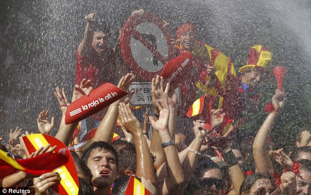 Hotting up: Supporters are sprayed with water as they wait for the team to arrive at Plaza Cibeles