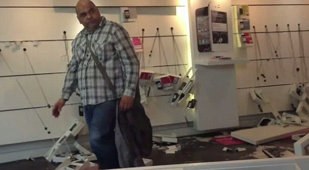 Menacing: The furious 42-year-old from Salford tears down the displays in the T-Mobile store
