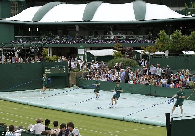 Back on: Grounds staff uncover a court  following a rain break for the Wimbledon Championships