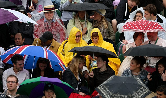 Taking shelter: Spectators brave the elements as the rain starts during the third round matches for the Wimbledon Championships