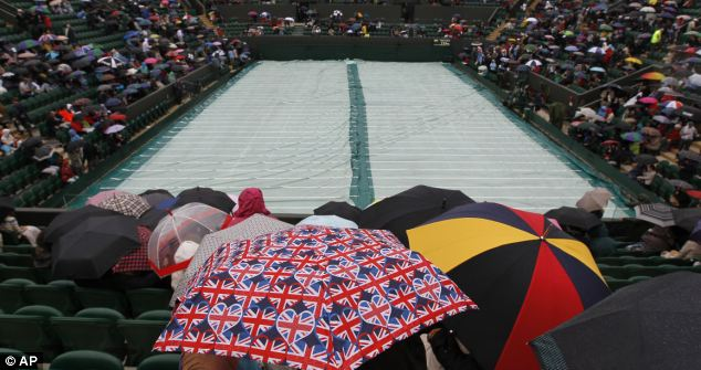 Take cover: Spectators shelter under umbrellas as rain delays play between Jo-Wilfried Tsonga of France and Mardy Fish of the US
