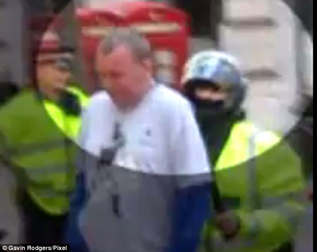 A video still shows the moment PC Harwood pushes Ian Tomlinson to the ground