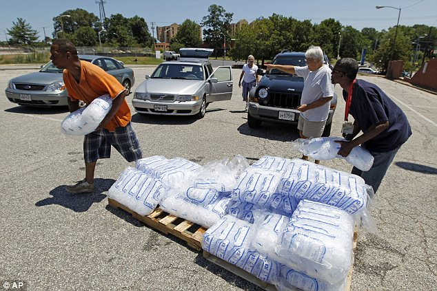 Aid: City workers George Kirk, right, and Joe Lane gave away free bags of ice to residents at the Northwood Plaza shopping center today in Baltimore