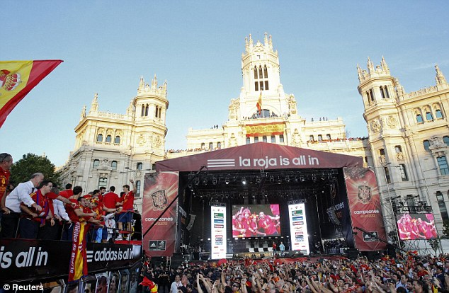 Centre stage: The procession eventually came to an end in downtown Madrid, at which point the players packed onto a stage to receive yet more adulation from the gathering crowd
