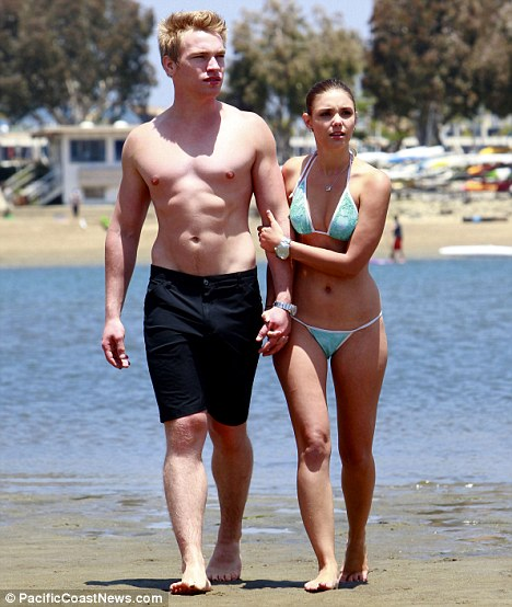 A protective arm: Heath grabbed Gruber tightly as they faced cameras on their beach outing